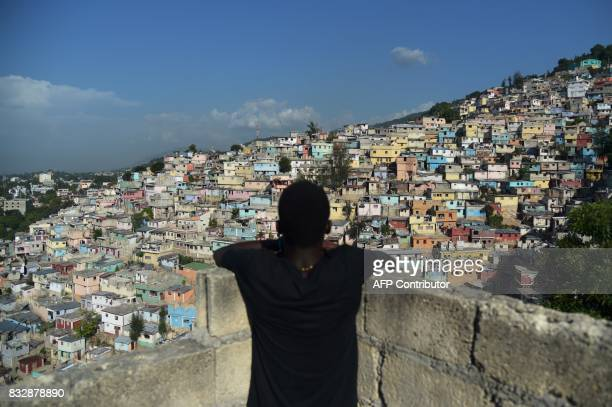 TOPSHOT A boy looks at the houses on the mountain in Jalousie neighborhood in PortauPrince on August 16 2017 / AFP PHOTO / HECTOR RETAMAL