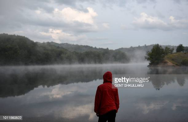 A boy looks at the mist over a mountain lake in Bize central Albania on August 5 2018 Albania is experiencing one of best tourist seasons ever with...