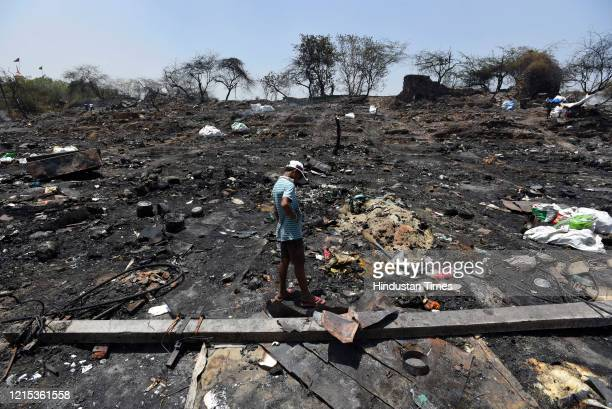 A boy looks for his belongings at the fire site in which around 1000 shanties burnt down and turned into ashes on Monday night at Tughlakabad...