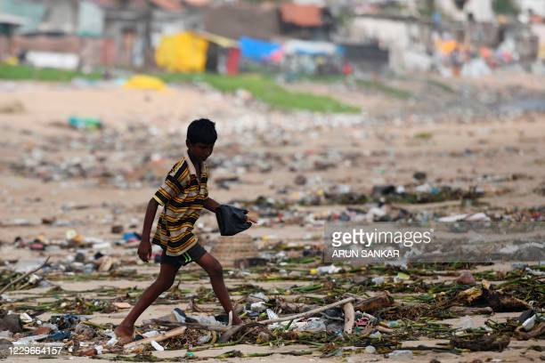 A boy looks for washedup plastic items from a beach after heavy rains in Chennai on November 18 2020