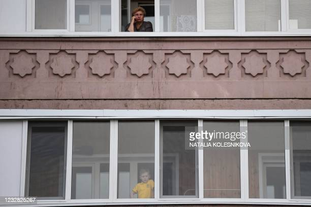 Boy looks from a balcony at people laying flowers and toys at a makeshift memorial for victims of the shooting at School No. 175 in Kazan on May 11,...