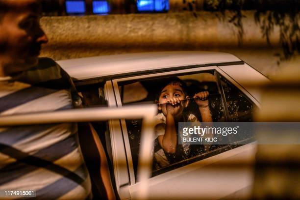 TOPSHOT A boy looks from a car as they prepare to leave after a mortar sent from Syrian side hit their house in Akcakale in Sanliurfa province on...