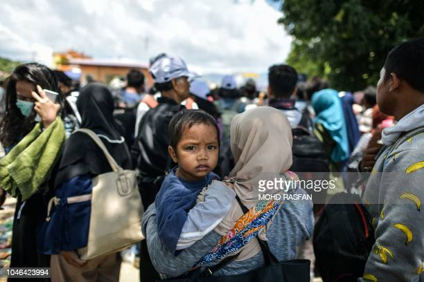 A boy looks on as he waits with his mother to board a military airplane for evacuations at the Mutiara SIS AlJufrie Airport in Palu Indonesia's...
