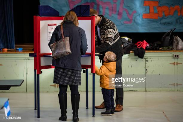 A boy looks on as his father fills in his ballot with his choice in the Democratic presidential primary elections at the Taylor Elementary School...