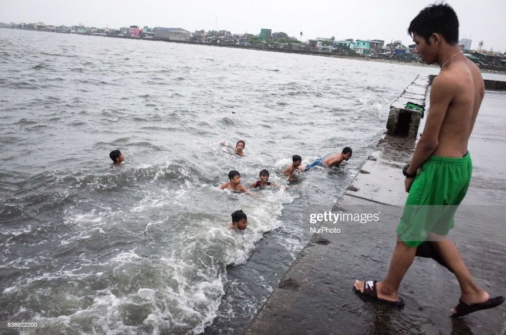 A boy looks on as his friends swim among the waves brought by Typhoon Pakhar along Manila Bay on Friday, August 25, 2017 in Navotas City, north of Manila, Philippines. Typhoon Pakhar is set to follow the same path as Typhoon Hato, threatening Hong Kong, Taiwan, and northern Philippines with heavy rain and strong winds.