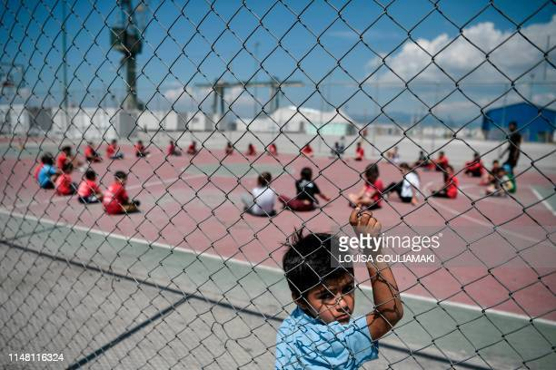 A boy looks on as refugee children play games at the Skaramangas camp on the outskirts of Athens on June 5 during an event organised by the Barca...