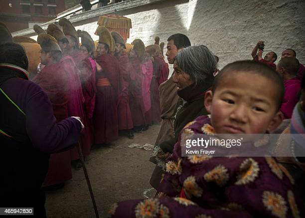 A boy looks on as Tibetan Buddhist Monks of the Gelug or Yellow Hat order carry a large thangka of Buddha after showing it to worshippers during...