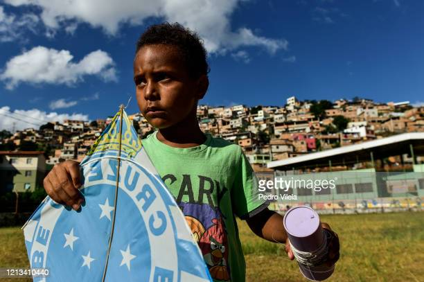 A boy looks on before flying a kite at favela Aglomerado da Serra on May 17 2020 in Belo Horizonte Brazil According to the Brazilian Health Ministry...