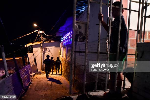A boy looks on Colombian soldiers during a patrol in the streets of Siloe neighborhood in Cali Colombia on December 13 2017 By order of Cali´s Mayor...
