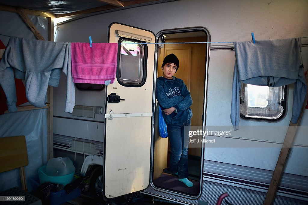 A boy looks out a camper van as migrants contend with wintery conditions in the camp known as the 'New Jungle' on December 1, 2015 in Calais, France. Thousands of migrants continue to live in the makeshift camp in the port town in northern France, where they continue to try and board vehicles heading for ferries or through the tunnel in an attempt to reach Britain.