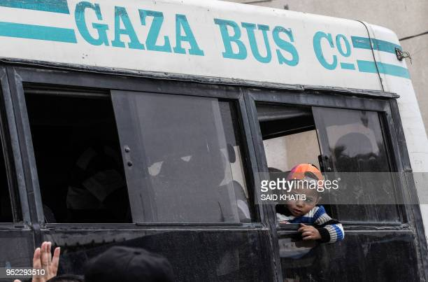 TOPSHOT A boy looks out from a window as he rides on a bus waiting in Khan Yunis to cross into Egypt from the Rafah border crossing in the southern...