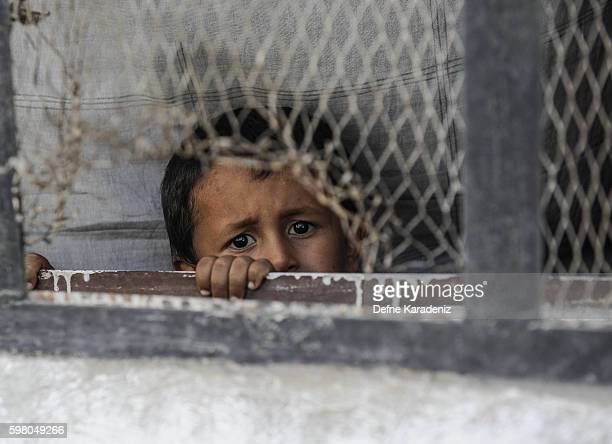 A boy looks out from a window of his home in the border town of Jarablus August 31 Syria Turkish troops and Turkeybacked rebels have been fighting...