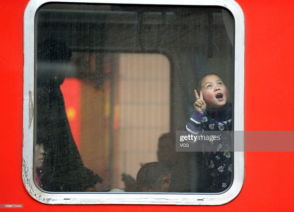 A boy looks out of the window of a train at Hangzhou Railway Station on January 22, 2013 in Hangzhou, China. China's annual Spring Festival travel rush will start on January 26 as authorities estimate 3.4 billion passenger journeys will be made for the Chinese lunar new year during the 40-day travel period.