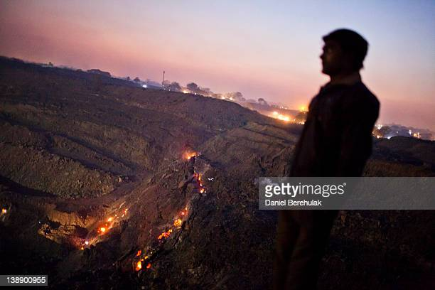 A boy looks out over an opencast coal mine as the glowing embers of an underground coal fire are seen below in the village of Guhanwadi on February...