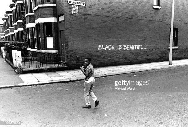 A boy looks over his shoulder on a street in Manchester where 'Black is Beautiful' is written on a wall 1969
