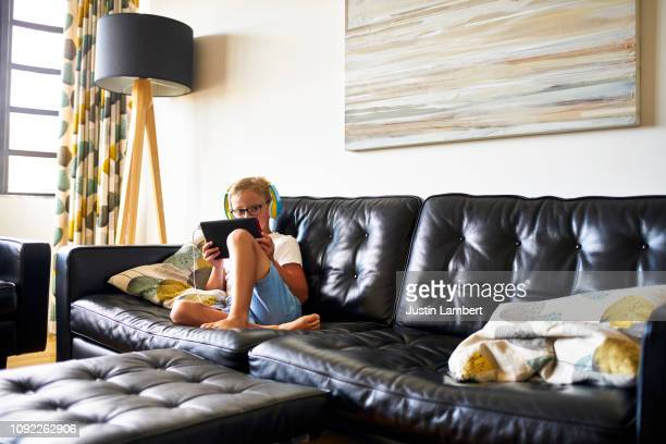 boy looks over tablet while sitting on the sofa with headphones on looking at the camera - saltdean stock pictures, royalty-free photos & images