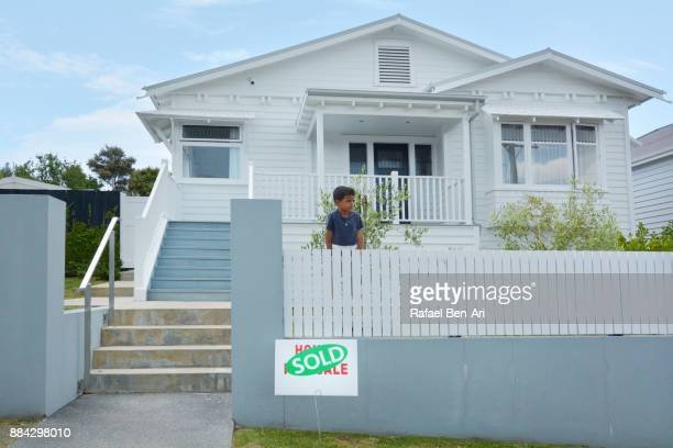 Boy looks over the fence over a sold sign in front of  traditional bungalow house