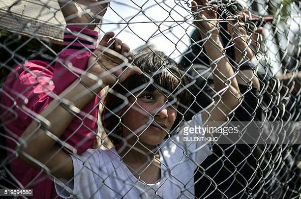 TOPSHOT A boy looks through a fence as migrants and refugees hold a protest to call for the reopening of the borders at the GreekMacedonian border in...