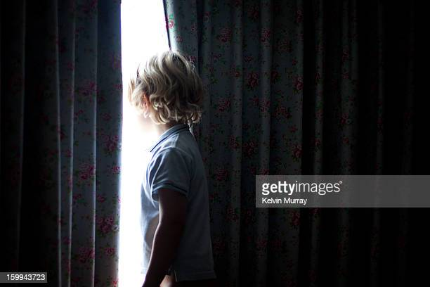boy looks through curtains out of window - looking through window stock pictures, royalty-free photos & images