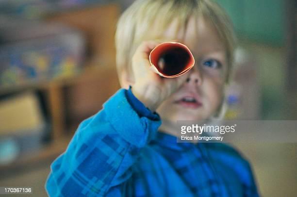 boy (4-6) looks through paper telescope at school