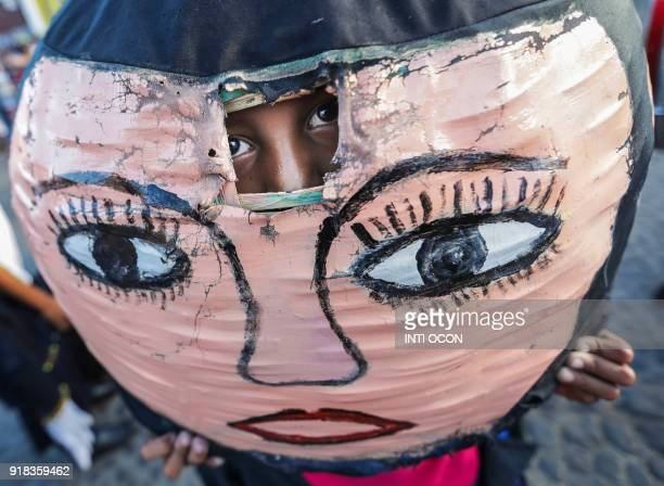 TOPSHOT A boy looks through the hole of a mask of the Enano Cabezon figure during the traditional dance parade during the XIV Poetry Festival in...