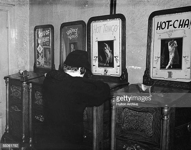 A boy looks through the viewer atop a peep show machine which plays the erotic International Mutoscope Reel Company production 'Hot Tango' early 20th...