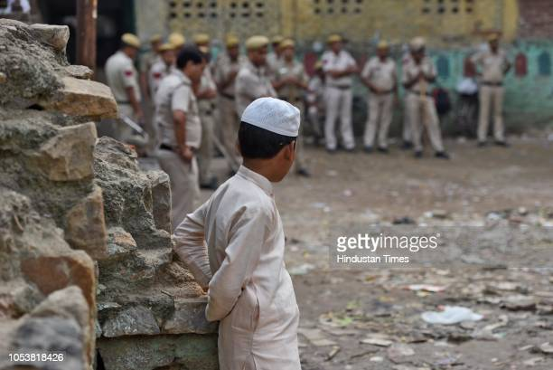 A boy looks towards the police deployment after an eightyearold student of a Madrasa died after he sustained a head injury during a scuffle between...