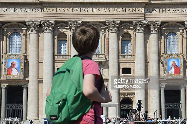 A boy looks towards the tapestries showing portraits of late Popes John Paul II and John XXIII hanged on the balconies of St Peter's basilica on...