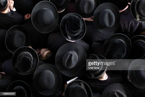 A boy looks up as Ultra Orthodox Jewish men pray next to the body of Rabbi Abraham Jacob Friedman of Sadigura Hasidic dynasty during his funeral on...