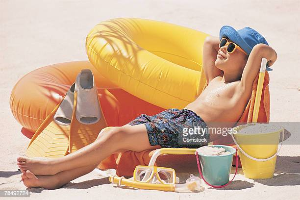 Boy lounging on beach with toys