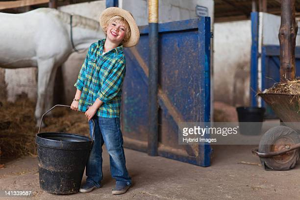 Boy lugging bucket in stable