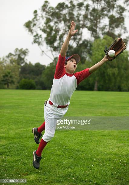 boy (10-12) lunging forward to reach baseball - diving to the ground stock pictures, royalty-free photos & images