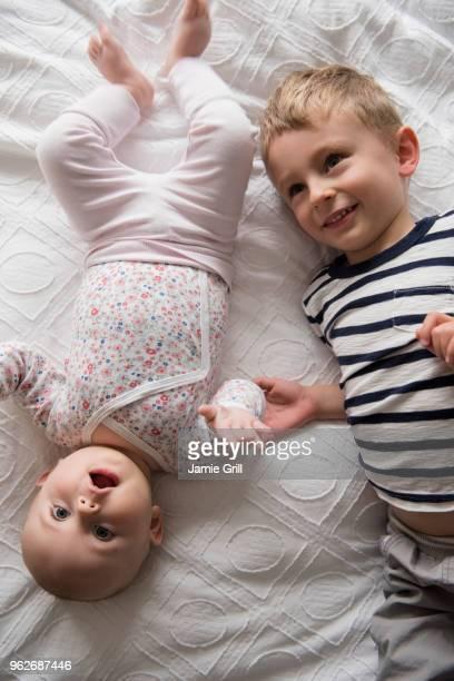 Boy lying beside little sister (18-23 months, 4-5)