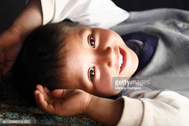 Boy (18-23 months) lying down and smiling, portrait, close-up