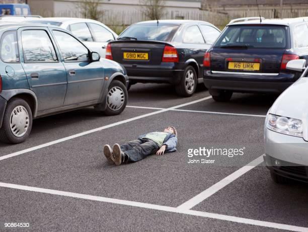 boy lying down in parking lot - parkfläche stock-fotos und bilder