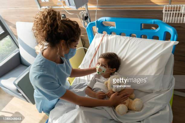 boy lying down on hospital bed and sweet nurse comforting him both wearing facemasks - child hospital stock pictures, royalty-free photos & images
