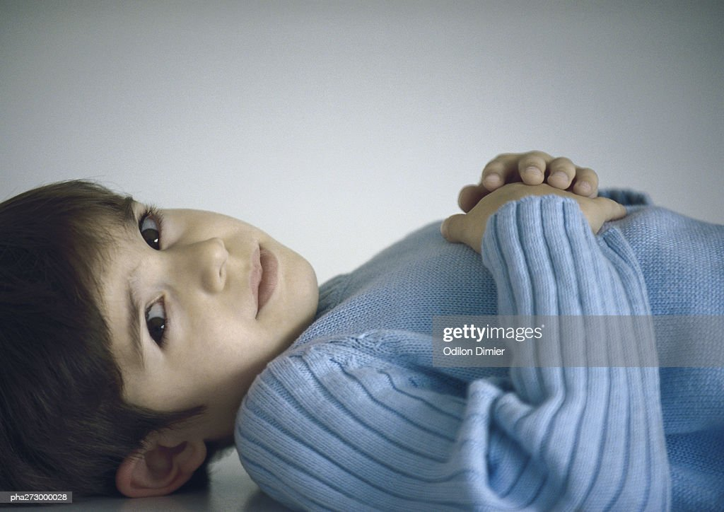 Boy lying down with hands on chest : Stockfoto