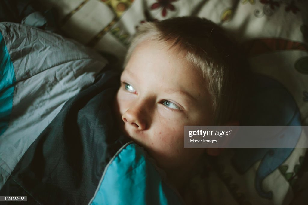 Boy lying in bed : Stock Photo