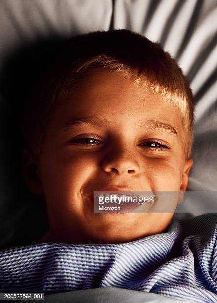 boy (5-7) lying in bed, smiling, portrait - microzoa stock pictures, royalty-free photos & images