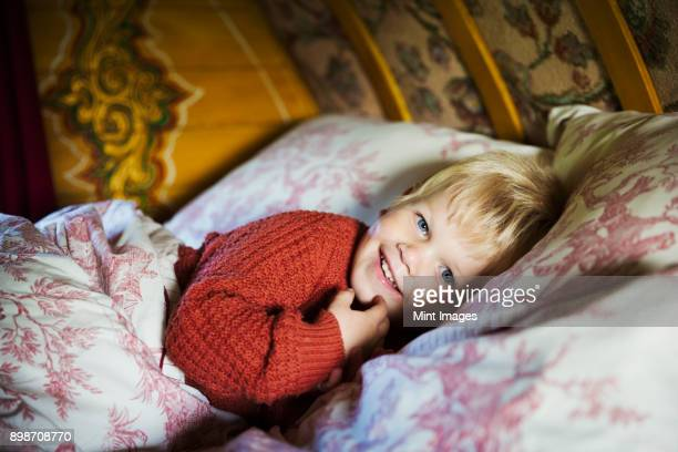 a boy lying in bed under a curved bow top roof of a gypsy caravan, looking at the camera. - gypsy caravan stock pictures, royalty-free photos & images