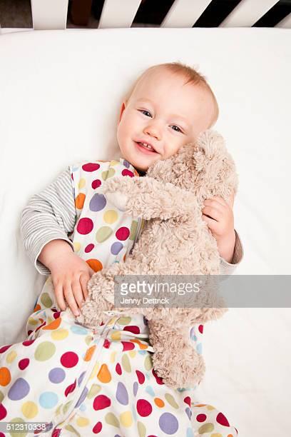 Boy lying in cot with teddy bear