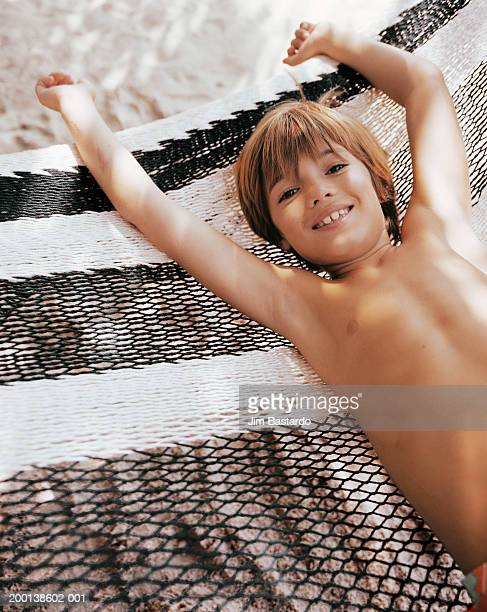 Boy (7-9) lying in hammock, smiling, elevated view, portrait