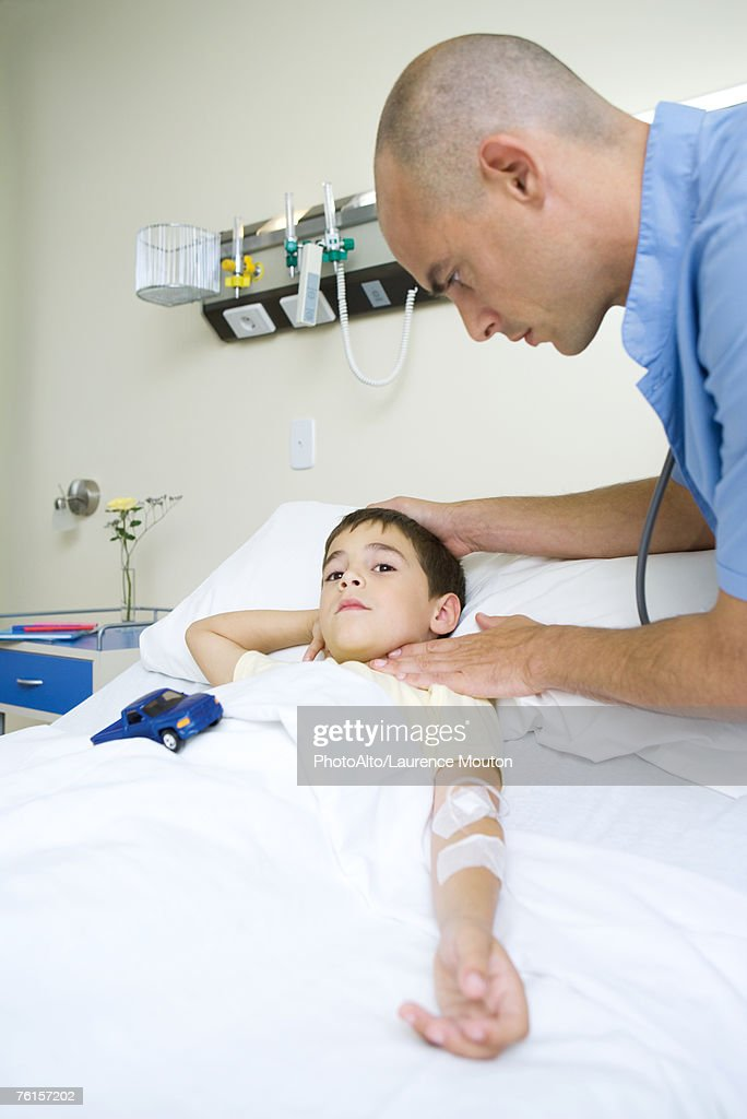 'Boy lying in hospital bed, doctor taking pulse' : Stock-Foto
