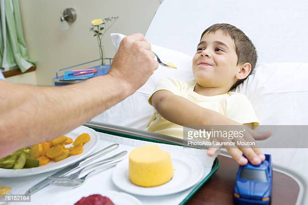 """""""boy lying in hospital bed, eating meal"""" - naughty nurse images stock photos and pictures"""