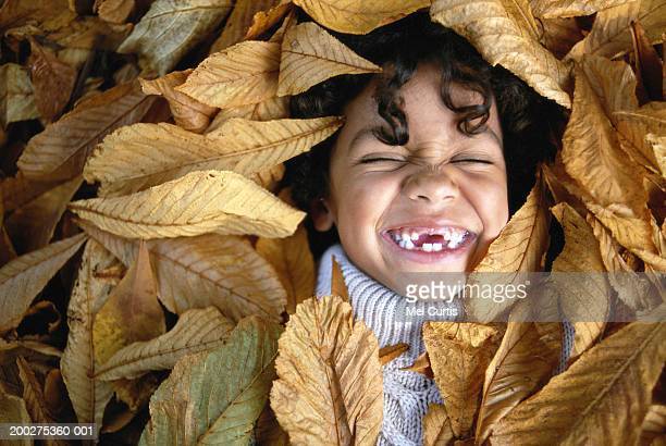 Boy (6-8) lying in leaves, laughing, eyes closed, overhead view