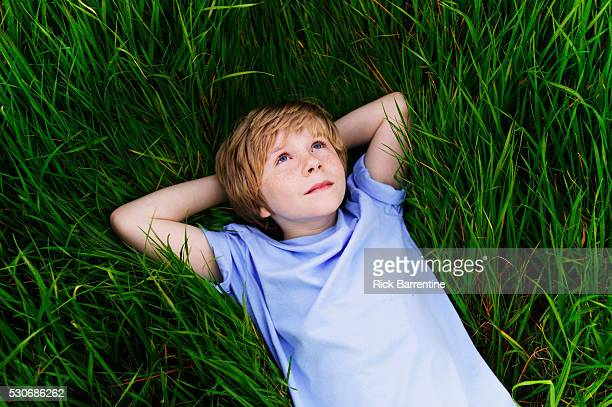 Boy Lying in Tall Grass