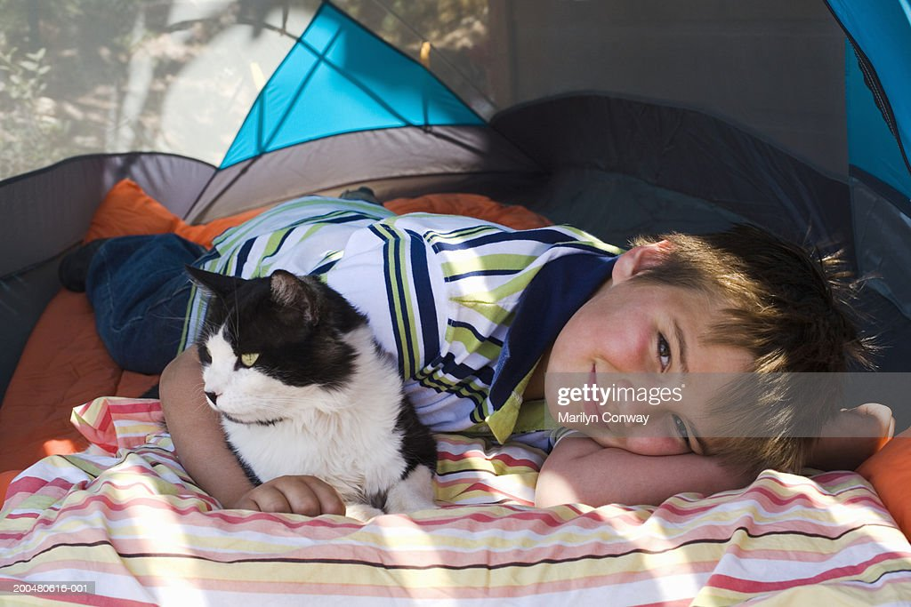 Boy (8-10) lying in tent with cat smiling portrait  & Boy Lying In Tent With Cat Smiling Portrait Stock Photo | Getty Images