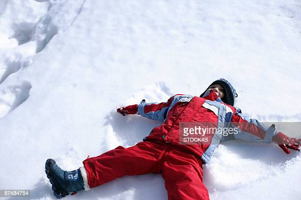 Boy lying in the snow and making an angel impression in the snow