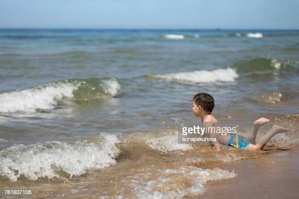 Boy lying in the surf on the beach, Corfu, Greece