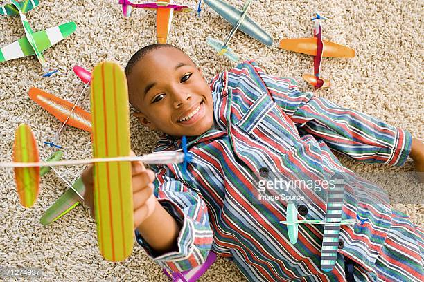 boy lying indoors playing with toy aeroplanes - a sense of home stock photos and pictures